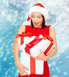 Woman in santa helper hat with many gift boxes Royalty Free Stock Image