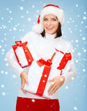 Woman in santa helper hat with many gift boxes Royalty Free Stock Images