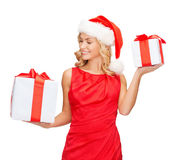 Woman in santa helper hat with many gift boxes Stock Photography
