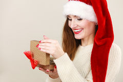 Woman in santa helper hat opening gift box Royalty Free Stock Photos