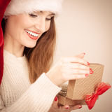 Woman in santa helper hat opening gift box Stock Photography