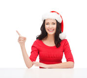 Woman in santa helper hat pointing to something Royalty Free Stock Photos