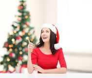 Woman in santa helper hat pointing to something Royalty Free Stock Image