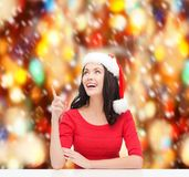 Woman in santa helper hat pointing to something Royalty Free Stock Images