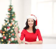 Woman in santa helper hat pointing to something Stock Images