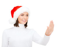 Woman in santa helper hat pressing vitrual button Royalty Free Stock Photos
