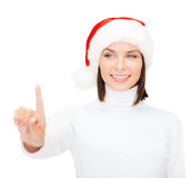 Woman in santa helper hat pressing vitrual button Stock Photo