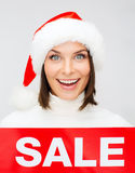 Woman in santa helper hat with red sale sign Royalty Free Stock Image