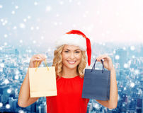 Woman in santa helper hat with shopping bags Stock Photos