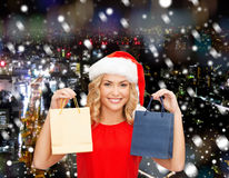 Woman in santa helper hat with shopping bags Royalty Free Stock Images