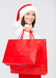 Woman in santa helper hat with shopping bags Stock Photography