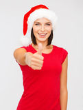 Woman in santa helper hat showing thumbs up Stock Photos