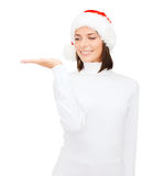 Woman in santa helper hat with something on palm Stock Photos