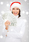 Woman in santa helper hat with us dollar money Royalty Free Stock Images