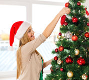 Woman in santa helper hats decorating a tree Stock Image