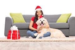 Woman with Santa hugging her dog Stock Photos