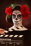 Woman in santa muerte mask behind clapboard Stock Photos