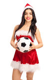 Woman in Santa outfit holding a football Royalty Free Stock Photography