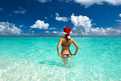 Woman in santa's hat at beach Stock Images