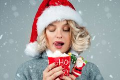Woman in santa`s hat is drinking coffee. Christmas mood. Beautiful woman in santa`s hat is drinking coffee. Christmas mood, winter and snowflakes around Stock Photos