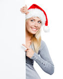 Woman in Santa's hat pointing at copyspace Royalty Free Stock Images