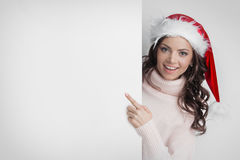 Woman in Santa`s hat pointing at copyspace Stock Photos