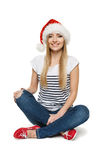 Woman in Santa's hat sitting on floor Stock Photo