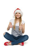 Woman in Santa's hat sitting on floor showing thumb up signs Stock Images