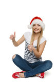 Woman in Santa's hat sitting on floor showing tumb up signs Stock Photography
