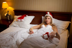 Woman in Santa's hats  remain all alone. Young woman in Santa's hats  with glass of champagne lying on bed remain all alone Royalty Free Stock Image