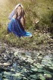 Woman in sari. Woman in Indian blue sari sitting outdoors near the water pond with water-lilies. Natural light and colors royalty free stock images