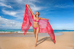 Woman sarong beach. Woman with pink sarong running on tropical beach blissful and free. beautiful woman in pink bikini on resort beach Stock Photos