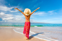 Woman sarong beach reaching. Woman with beautiful pink sarong on tropical beach enjoying her freedom happy Royalty Free Stock Images