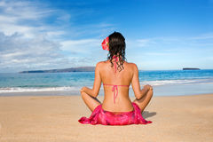 Woman sarong meditiate beach. Woman with beautiful pink sarong and bikini mediating and practicing yoga on tropical beach Royalty Free Stock Image