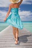 Woman sarong resort. Beautiful woman walking down tropical resort pier in sarong Stock Photography