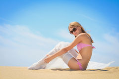 Woman with sarong sitting on the beach Royalty Free Stock Image