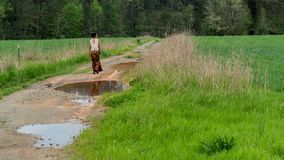 Woman in sarong walking on dirt road with puddles in field stock photos