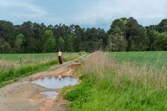Woman in sarong walking on dirt road with puddles in field stock photography