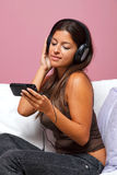 Woman sat in an armchair listening to music Stock Photos