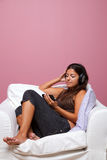Woman sat in an armchair listening to music Stock Photography