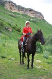 Woman sat on horse. Russian woman sat on horse in countryside, cliffs in background, North Caucasus, Asia Stock Images