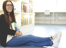 Woman sat on library floor with straight legs Royalty Free Stock Image