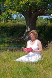 Woman sat in a meadow reading a book Royalty Free Stock Images