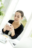 Woman sat at table checking mobile phone Royalty Free Stock Photos