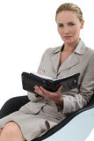 Woman sat taking notes. Blond woman sat in chair taking notes stock image