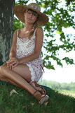 Woman sat by tree Stock Photos
