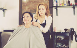 Woman is satisfied with work of young haircutter Royalty Free Stock Image