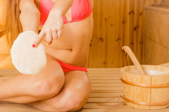 Woman in sauna with exfoliating glove. Skincare. Closeup of woman in wood finnish spa sauna with exfoliating glove. Girl in bikini relaxing. Skin care concept Stock Photos