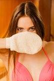 Woman in sauna with exfoliating glove. Skincare. Funny young woman in wood finnish spa sauna with exfoliating glove. Girl in bikini relaxing. Skin care concept Royalty Free Stock Photo