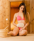 Woman in sauna with exfoliating glove. Skincare. Royalty Free Stock Images